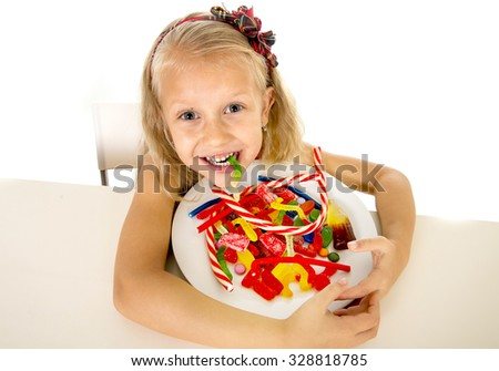 pretty happy Caucasian female child eating dish full of candy holding the dish in sweet sugar abuse dangerous diet and unhealthy nutrition concept isolated on white background - stock photo