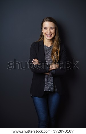 Pretty happy confident young woman in casual jeans leaning back against a dark wall with folded arms smiling at the camera