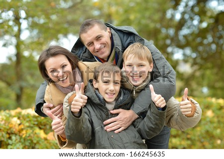 pretty happy family for a walk in the park fall - stock photo