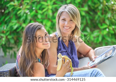 pretty happy girl enjoying a banana with her smiling blond mother reading a book - stock photo