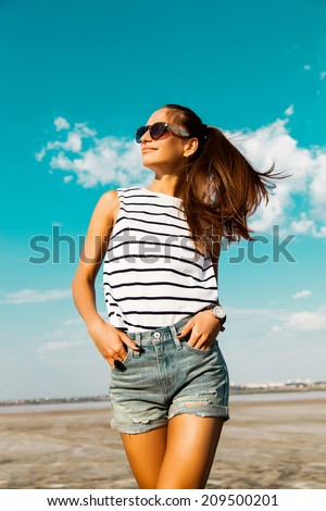 Pretty happy girl in a striped T-shirt and jeans shorts posing with glasses on the background of a summer blue sky. - stock photo
