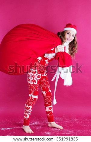 Pretty happy girl is holding big bag with gifts on her back isolated on red background