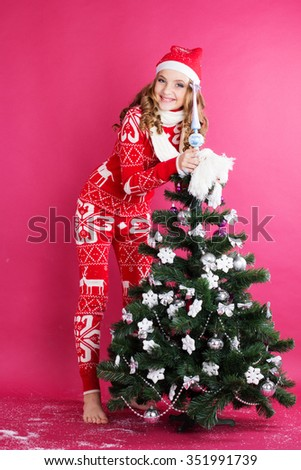 Pretty happy girl is looks out from behind christmas tree - stock photo