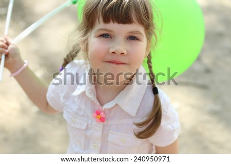 Pretty happy little girl holds green balloons at sunny day outdoor - stock photo