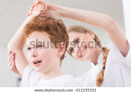 Pretty happy physiotherapist glad of results in boy's physiotherapy of injured shoulder - stock photo