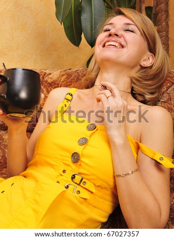 Pretty happy relaxed young lady sitting with coffee cup on couch - stock photo