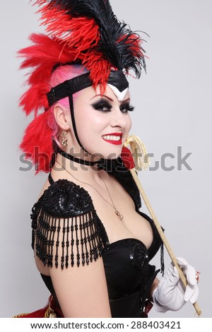 Pretty happy smiling bourlesque girl in fancy costume with plumage - stock photo