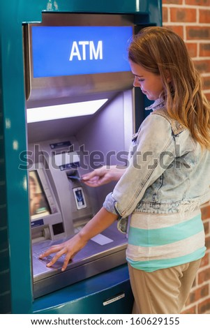 Pretty happy student withdrawing cash at an ATM - stock photo