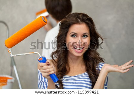 Pretty happy woman looking at camera while her husband painting wall - stock photo