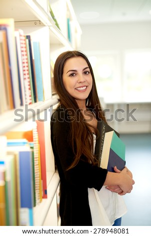 Pretty happy young female university student doing research in the campus library standing holding a large text book in her hands smiling at the camera - stock photo