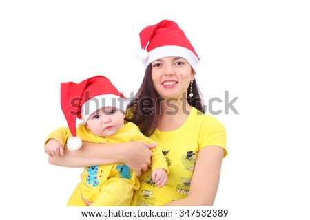 pretty happy young mother with the cute little baby dressed in new year caps - stock photo