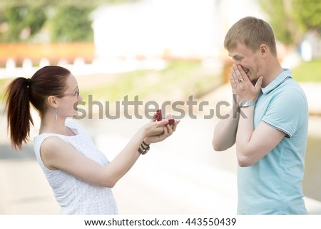 Pretty happy young woman requesting a hand of her beloved boyfriend, asking to marry. She is holding red box with an engagement ring smiling at surprised man in park on a sunny warm day - stock photo