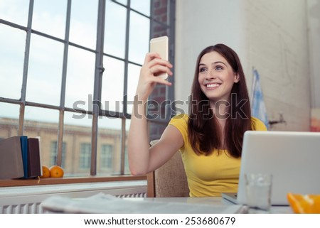 Pretty happy young woman sitting at a table at home with her laptop taking a selfie on her mobile phone - stock photo