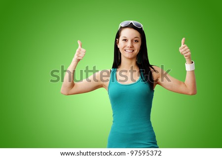 Pretty healthy and lean young woman smiling giving two thumbs up over gradient green background: perfect for weight loss or other achievement. - stock photo