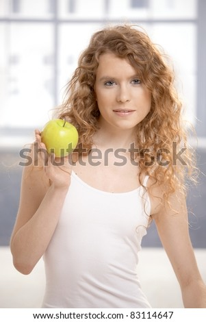 Pretty, healthy girl after workout, holding apple in her hand.? - stock photo