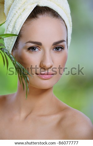 pretty healthy woman touches face green  tropical  leaf - stock photo