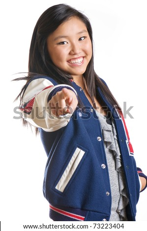 Pretty, high energy teen girl wearing school jacket and pointing at the camera - stock photo