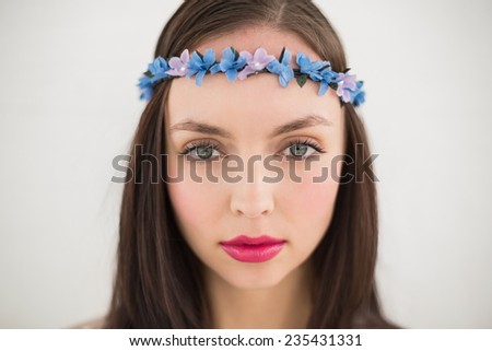 Pretty hippie looking at camera against grey wall - stock photo
