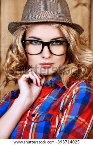 Pretty hipster girl in hat and glasses posing by a wooden wall. Youth style, fashion. - stock photo