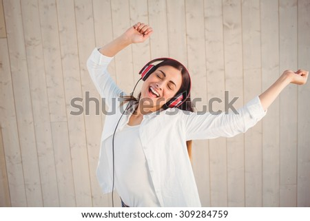 Pretty hipster listening to music on wooden planks background