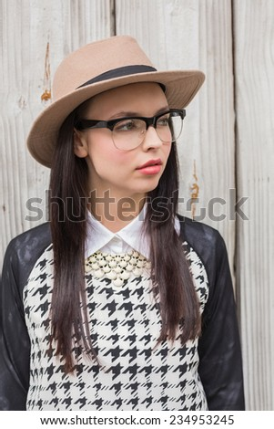 Pretty hipster posing for camera against bleached wooden planks