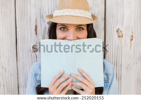 Pretty hipster reading a book against bleached wooden fence - stock photo