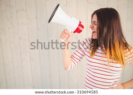 Pretty hipster shouting through megaphone on wooden planks background - stock photo