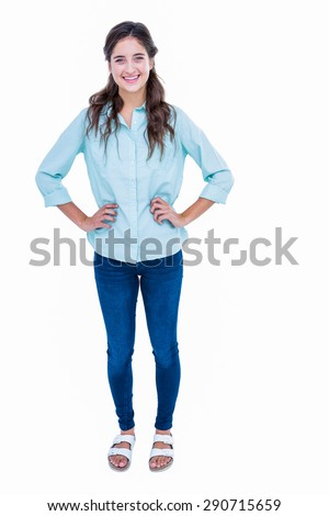 Pretty hipster with hands on hips smiling at camera on white background - stock photo