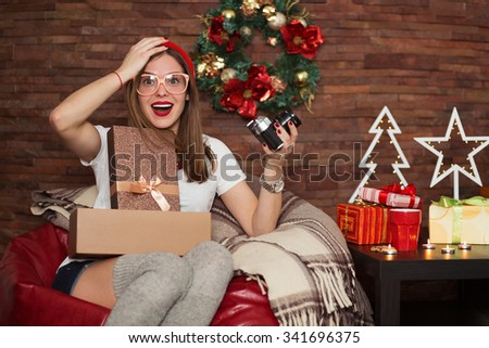 Pretty hipster woman opening her Christmas presents - stock photo