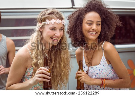 Pretty hipsters toasting with beer on a summers day - stock photo