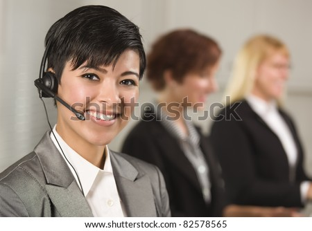 Pretty Hispanic Businesswoman with Colleagues Behind in an Office Setting. - stock photo