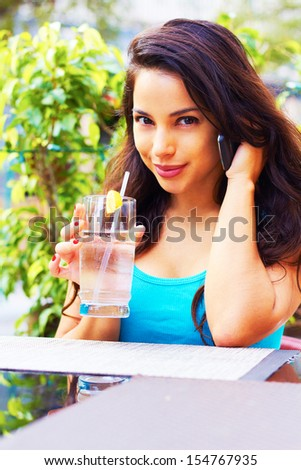 Pretty hispanic female drinking water at restaurant while on cell phone. - stock photo