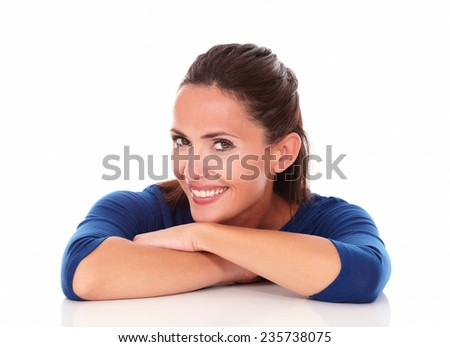 Pretty hispanic looking at you with arms crossed and smiling in white background - stock photo