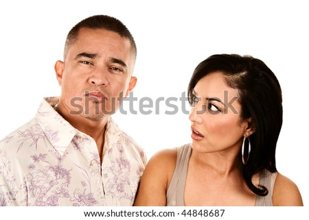 Pretty Hispanic wife looks suspiciously at her handsome husband - stock photo