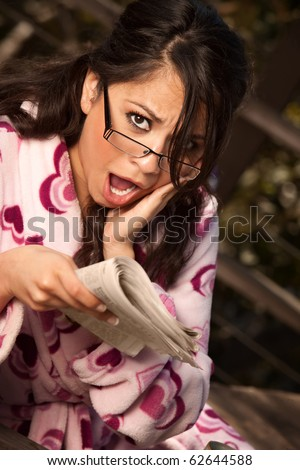 Pretty Hispanic Woman in Bathrobe Sitting Outdoors Reacts to Newspaper - stock photo