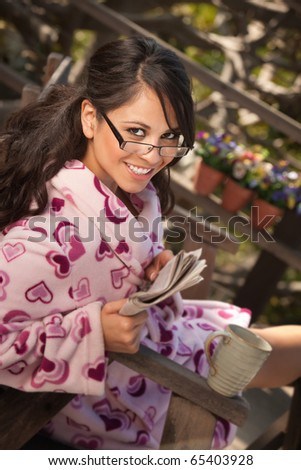 Pretty Hispanic Woman in Bathrobe Sitting Outdoors with Tea or Coffee - stock photo