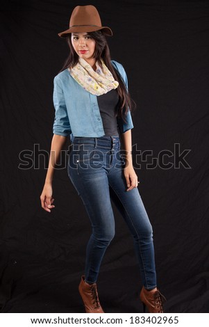 Pretty Hispanic woman in blue jeans, a blue vest and a hat, standing and looking at the camera with a friendly, happy gaze