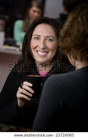 Pretty Hispanic woman in cafe with cup of coffee or tea - stock photo