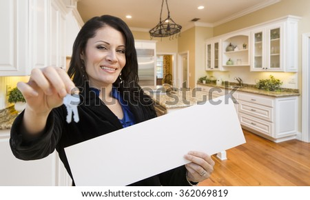 Pretty Hispanic Woman In Kitchen Holding House Keys and Blank White Sign.