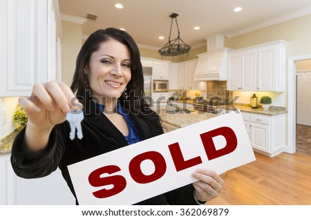 Pretty Hispanic Woman In Kitchen Holding House Keys and Sold Sign. - stock photo