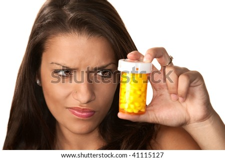 Pretty Hispanic woman reading label on prescription medication - stock photo