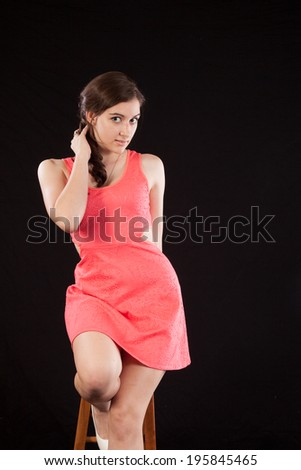 Pretty Hispanic woman sitting on a wooden stool and looking at the camera with a happy, pleased smile,
