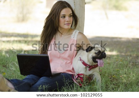 Pretty hispanic woman spending some time with her pug dog at the park - stock photo