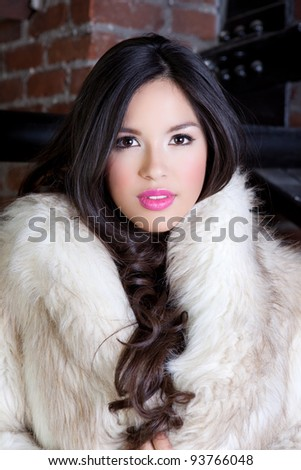 Pretty Hispanic Woman with Beautiful Long Hair sitting in the quiet space of a circle window - stock photo