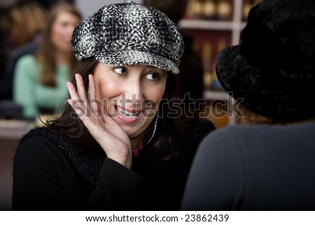Pretty Hispanic woman with coffee sharing gossip - stock photo