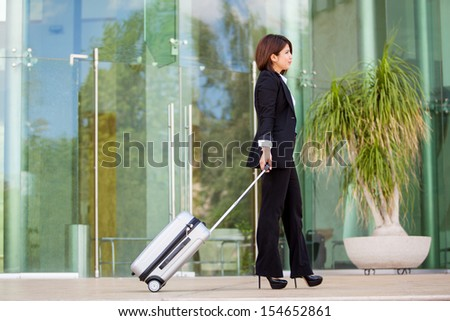 Pretty Hispanic young woman on a suit traveling with a suitcase