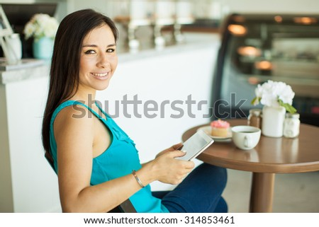 Pretty Hispanic young woman relaxing and reading on a tablet computer at a coffee shop