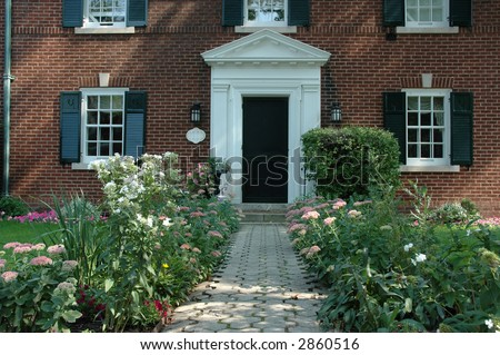 Pretty house / home entrance with flowers and black shutters - stock photo