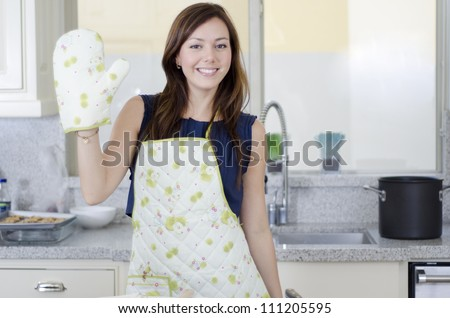 Pretty housewife waving with oven gloves on
