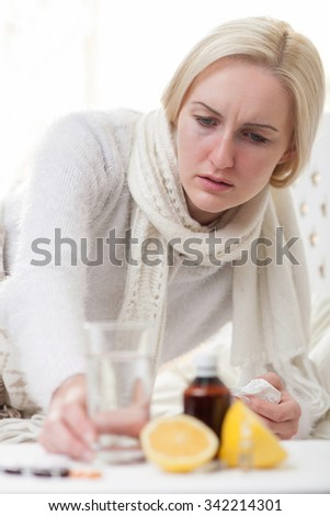 Pretty ill girl is taking a glass of water from the table near pills and vitamins. She is lying on bed and holding napkin. The lady is looking forward with depression - stock photo